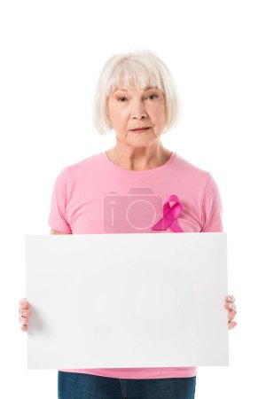 senior woman in pink t-shirt with breast cancer awareness ribbon holding blank banner and looking at camera isolated on white