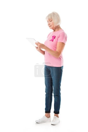 senior woman in pink t-shirt with breast cancer awareness ribbon using digital tablet isolated on white