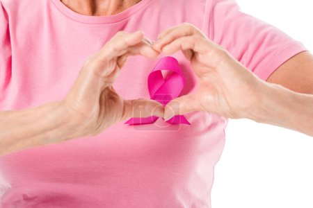 cropped shot of senior woman in pink t-shirt with breast cancer awareness ribbon showing hand heart symbol isolated on white