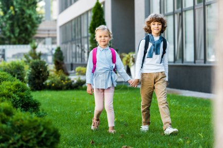 adorable schoolkids with backpacks holding hands and walking on green lawn