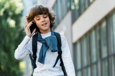 low angle view of schoolboy with backpack talking by smartphone and looking down