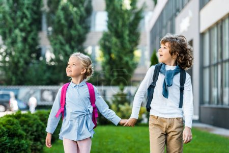 adorable excited schoolkids with backpacks holding hands and looking up