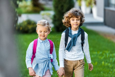 adorable happy little schoolkids holding hands and walking on green lawn