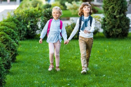 full length view of adorable happy schoolkids with backpacks holding hands and walking on green lawn
