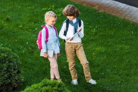 high angle view of children with backpacks holding digital tablet while standing together on green lawn