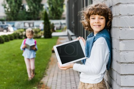cute happy boy holding digital tablet with blank screen and smiling at camera