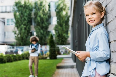 cute little schoolgirl using digital tablet and smiling at camera while leaning at brick wall