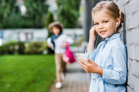 cute little child in earphones using smartphone and smiling at camera