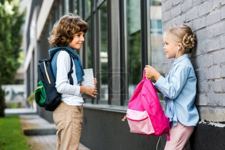 cute little schoolchildren with backpacks smiling each other outside