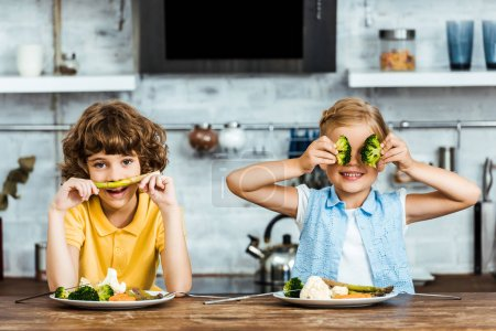 cute little kids sitting at table and having fun with vegetables