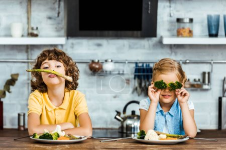 Photo for Adorable children playing with vegetables while sitting together at table - Royalty Free Image