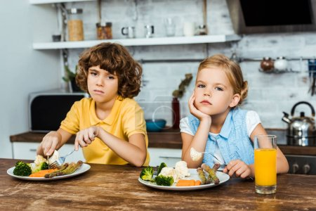 Photo for Bored children eating vegetables and looking at camera - Royalty Free Image