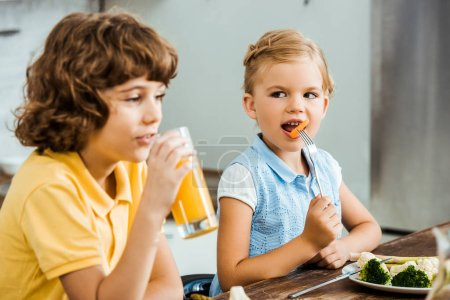 cute little children eating vegetables and drinking juice