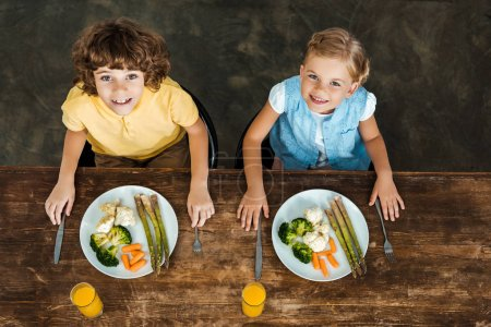 high angle view of adorable happy kids eating healthy vegetables and smiling at camera