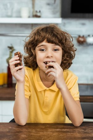 Photo for Cute happy boy eating delicious chocolate with nuts and smiling at camera - Royalty Free Image