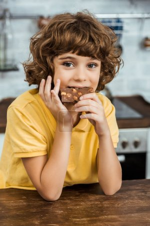 cute little boy eating chocolate with hazelnuts and looking at camera