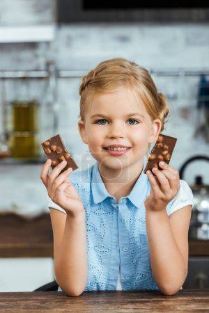 Photo for Adorable happy child holding pieces of delicious chocolate and smiling at camera - Royalty Free Image