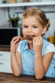 adorable child eating delicious chocolate with hazelnuts and smiling at camera