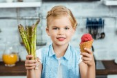 adorable happy child holding delicious ice cream cone and healthy asparagus, smiling at camera