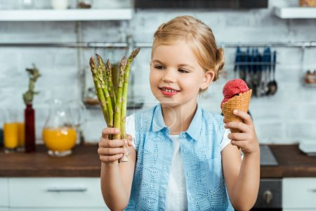 cute smiling child holding delicious ice cream cone and healthy asparagus