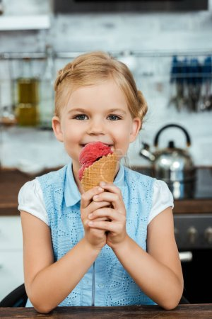 beautiful happy child eating delicious ice cream and smiling at camera