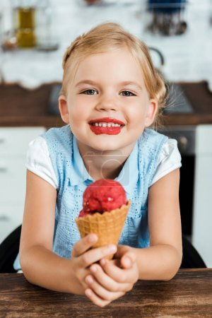 adorable happy kid holding delicious sweet ice cream cone and smiling at camera