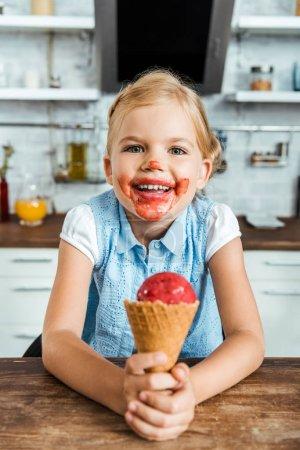 Photo pour Adorable enfant heureux tenant délicieux cône de crème glacée et souriant à la caméra - image libre de droit