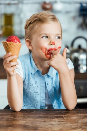 adorable little child eating sweet ice cream and licking finger