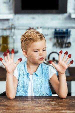 mignon petit enfant assis à table et en regardant les mûres framboises fraîches sur les doigts