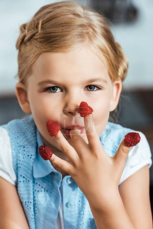 adorable child eating raspberries and looking at camera