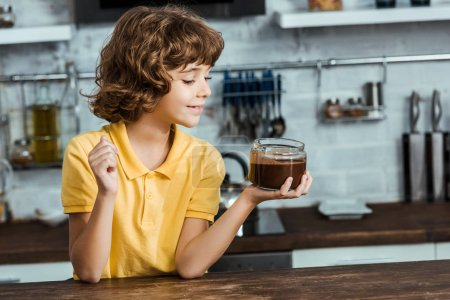 cute happy little boy holding glass jar with delicious chocolate spread
