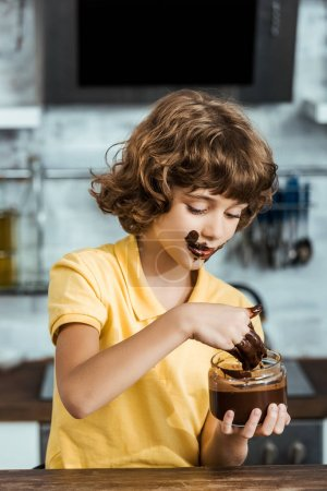 cute little boy eating sweet chocolate spread from glass jar