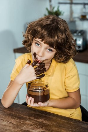 cute little boy eating sweet chocolate spread from glass jar and looking at camera
