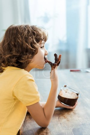 side view of cute little boy licking finger with delicious chocolate spread