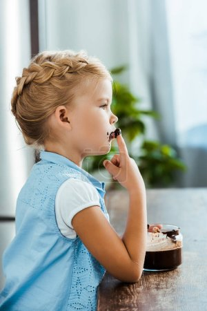 side view of cute little child eating delicious chocolate spread and looking away