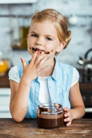 cute little child eating delicious chocolate spread and looking at camera