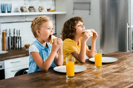 beautiful children sitting at table and eating tasty sandwiches