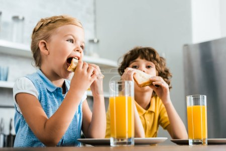 Photo for Low angle view of cute little kids eating tasty sandwiches - Royalty Free Image