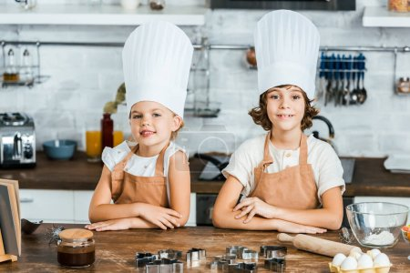 cute happy children in aprons and chef hats smiling at camera while cooking together in kitchen