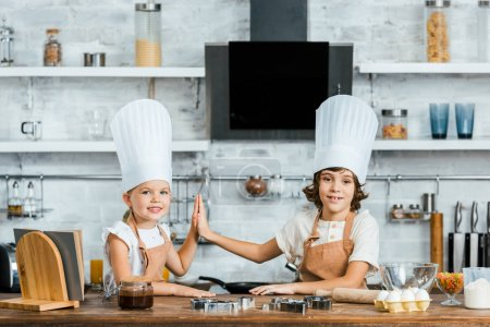 adorable children in chef hats and aprons giving high five and smiling at camera while cooking together in kitchen