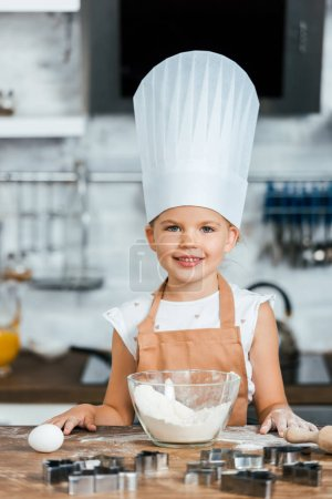 cute happy child in apron and chef hat cooking dough and smiling at camera