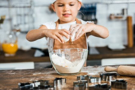 Photo for Cute smiling child in apron preparing dough for cookies - Royalty Free Image