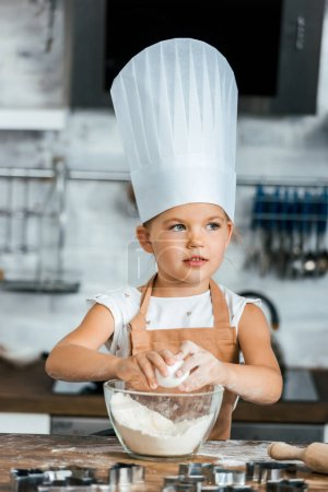 adorable child in aron and chef hat cooking dough and looking away in kitchen