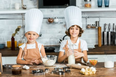 cute little children in chef hats and aprons preparing dough for cookies and smiling at camera