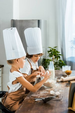 side view of cute little children in chef hats and aprons preparing dough for cookies together