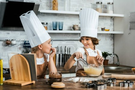 Photo for Adorable children in chef hats and aprons smiling each other while preparing dough for cookies - Royalty Free Image