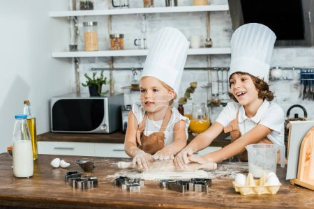 Photo for Cute happy children in chef hats preparing dough for cookies and looking away - Royalty Free Image
