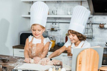cute happy children in chef hats preparing dough for cookies