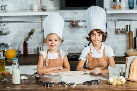 cute happy children in chef hats preparing dough for cookies and smiling at camera