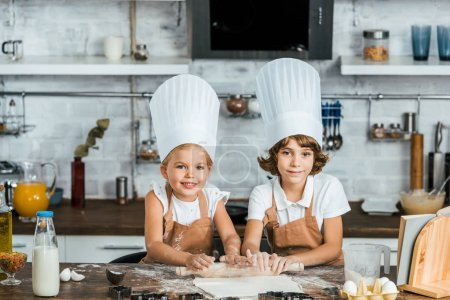 Photo for Adorable happy kids in chef hats preparing dough for cookies and smiling at camera - Royalty Free Image